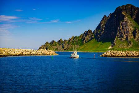 Seascape with fishing boat and stone breakwater, Bleik village, Andoya island, Vesteralen archipelago. Stock Photo