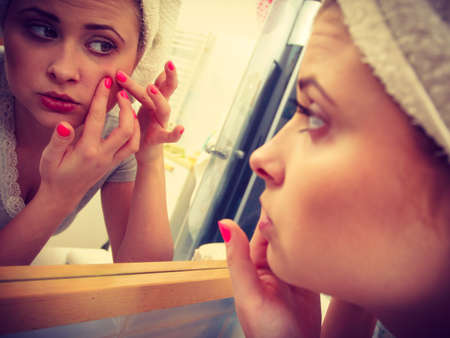 Woman looking at her reflection in mirror thinking about her complexes having serious face expression, analyzing face skin complexion squeezing pimples Stock Photo