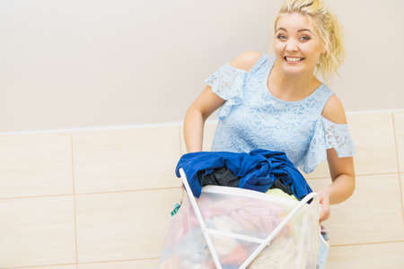 Woman having troubles with holding big laundry basket full of colorful dirty clothes. Bathroom utensils concept. Stock Photo