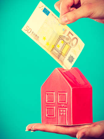 Household savings and finances, economy concept. Preson puts money into piggy bank in the shape of house, studio shot on blue background 版權商用圖片