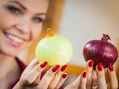 Woman holding healthy, fresh natural red and white onion. Healthy eating and dieting concept.