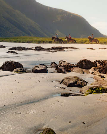 Scenic sea coast with people riding on horse back at Gimsoysand sandy beach. Nordland county, Lofoten archipelago Norway. Tourist attraction.