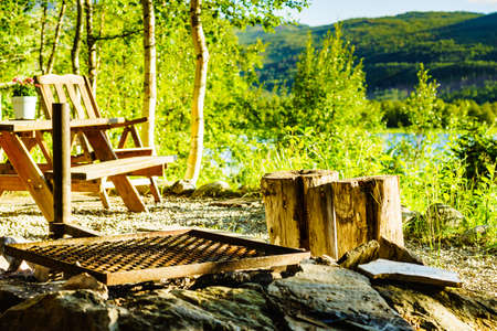 Picnic site rest stop area wooden chairs and table with flowers decoration on norwegian lake fjord shore. Holidays relaxation on trip. Scandinavia Europe. 版權商用圖片