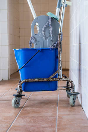 Trolley with bucket full of water and mop. Household or industrial cleaning objects.