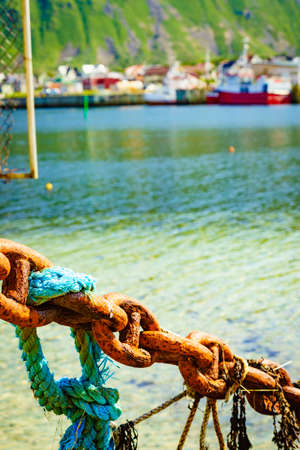 Rusty old metal chain links in port. Marine details. Bleik village in the background. Banque d'images