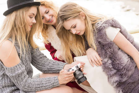 Female photographer showing fashion models results of photo shoot. Behind the scenes of professional modeling and photography industry. Archivio Fotografico