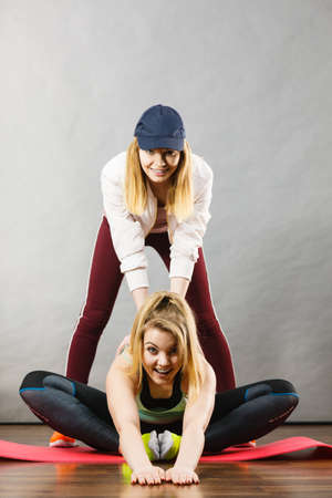 Young blonde woman in sportswear sitting on wooden floor indoor stretching legs with her female trainer. Training at home, being fit and healthy. 版權商用圖片
