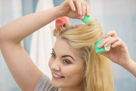 Blonde woman using hair rollers to create beautiful hairstyle on her hairdo. Фото со стока