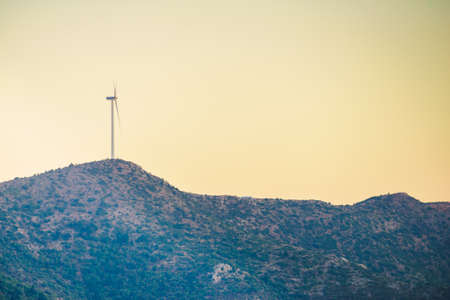 Windmill on Greek hills. Wind farm, source of renewable green energy in Europe. Ecologogy concept.