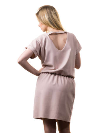 Fashionable pretty woman wearing elegant casual pink tunic dress presenting stylish elegant outfit. Back view with triangle shaped hole.