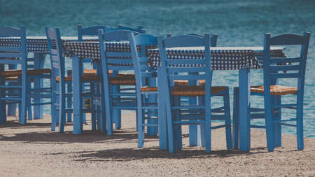 Seaside blue table and chairs open cafe outdoor restaurant in Greece on sea shore. Summer vacation on resort. 版權商用圖片