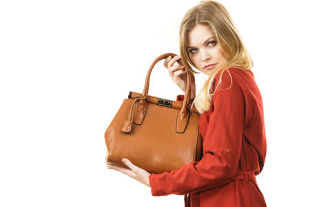 Woman protecting her handbag from thieves. Youn female guarding expensive leather bag