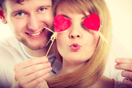 Love and happiness concept. Cheerful enjoyable young couple with little small hearts on sticks covering woman man eyes. Lovers blinded by their big love. Banque d'images