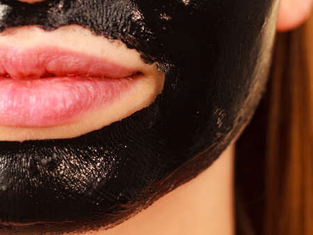 Close up woman with carbo detox black peel-off mask on her face, detail view. Teen girl taking care of oily skin, cleaning the pores. Beauty treatment. Skincare.