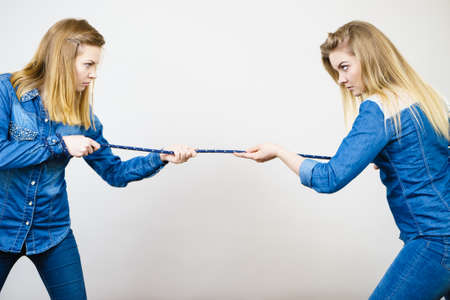Two women having argue pulling rope being mad at each other. Bad rivalry relationship. Stockfoto