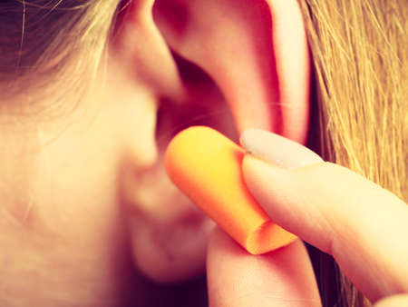 Woman putting ear plugs into her ears getting rid on noise in loud place.