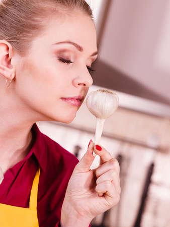 Frau, die gesundes Kraut hält, zwei frischer natürlicher Knoblauch, der es riecht. Gesundes Essen und Diätkonzept.
