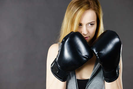 Sportsmanship fairplay and strong body. Young woman fighting boxing. Blonde girl wearing black punch gloves. Sport and fitness, power, exercising. Stock Photo