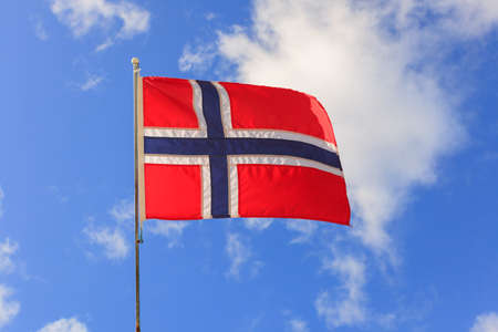 The norwegian flag waving against blue sky Imagens