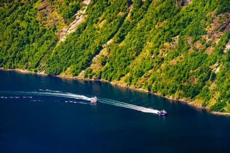 Tourism vacation and travel. Mountains landscape and cruising ship on fjord in Norway Scandinavia.