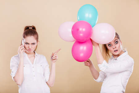 Two girls with colorful balloons and mobile phone. Best friends preparing party celebration, having problem, bad relationship Banque d'images
