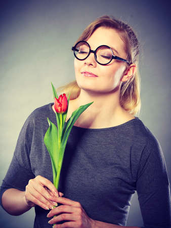 Peace and content. Beauty adorable girl smelling beautiful spring flower. Peaceful enjoyable woman with red green tulip. Lady smell nature. Stock Photo
