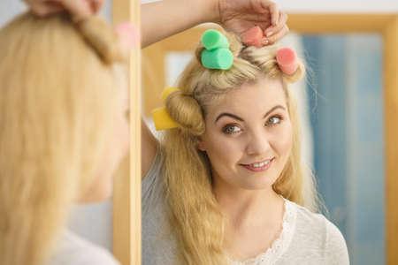 Blonde woman using hair rollers to create beautiful hairstyle on her hairdo. Zdjęcie Seryjne
