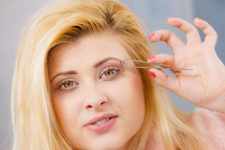 Woman plucking eyebrows depilating with tweezers closeup part of face. Girl tweezing removing her facial hairs..
