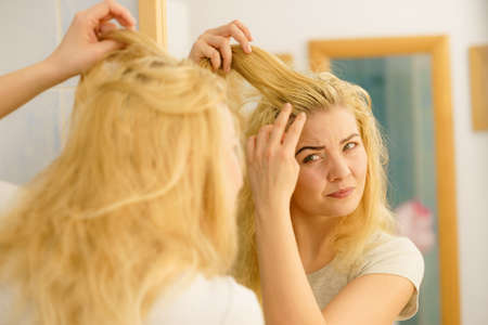 Blonde woman having problems with greasy oily hair looking at herself in bathroom. Female showing scalp, scratching herself, dandruff problem. Imagens