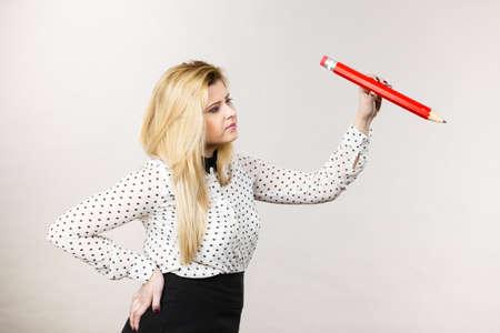 Positive woman blonde student girl or female teacher wearing dotted shirt holding big red pencil drawing. Studio shot on grey Reklamní fotografie