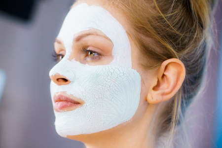 Woman with green mud mask on face. Teen girl taking care of oily skin, purifying the pores. Beauty treatment. Skincare.
