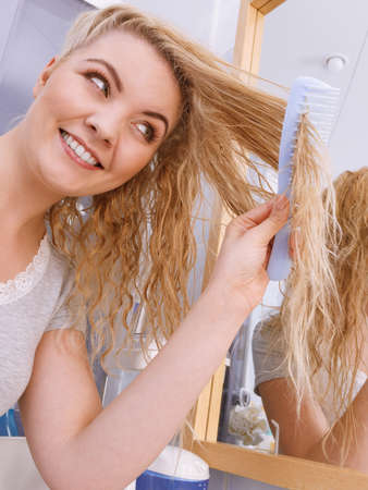Woman combing after bath her long wet curly hair in bathroom, looking in mirror. Blonde girl taking care refreshing her hairstyle in morning. Haircare concept.