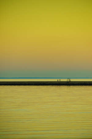 Seascape at sunset with people walking on breakwater. Denmark coastline.