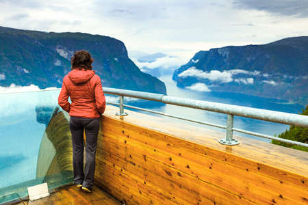 Tourist woman enjoying fjord view Aurlandsfjord landscape from Stegastein viewing point. Norway Scandinavia. National tourist route Aurlandsfjellet. Reklamní fotografie