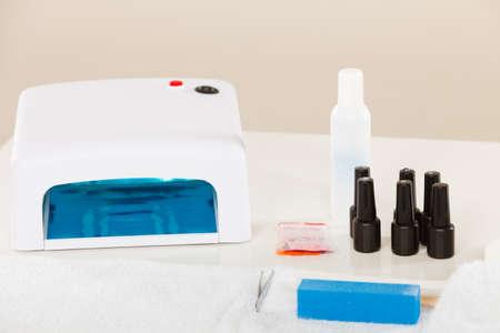 Manicure ibrida gel professionale con lampada uv a led impostata presso il salone di estetista. Concetto di oggetti di trattamento di bellezza benessere spa