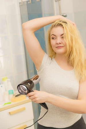 Frau, die nasse Achselhöhle unter Verwendung des Haartrockners trocknet. Schweiß und Geruch loswerden, Hyperhidrose. Standard-Bild
