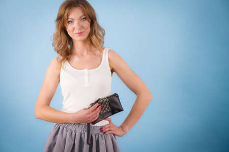 Happy young elegant woman holding purse wallet ready for shopping or party