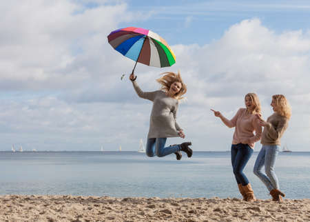Female jumping with colorful umbrella her two friends are making fun of her laughing and looking.