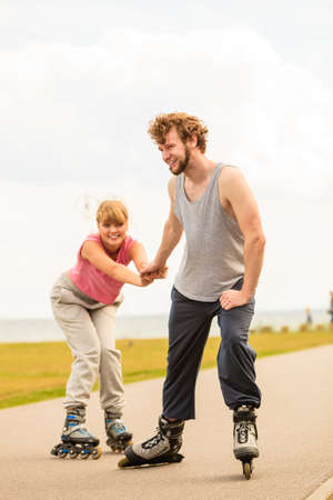 Active lifestyle people and freedom concept. Young fit couple on roller skates riding outdoors on sea coast, woman and man enjoying time together. 写真素材
