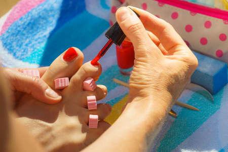 Frau, die ihre Pediküre mit rotem Nagellack auf Strandtuch entspannt. Frau kümmert sich um Füße
