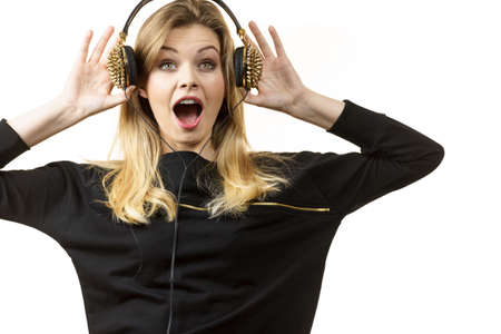 Surprised young woman wearing grunge headphones with spikes being amazed or suprised with what she is listening.