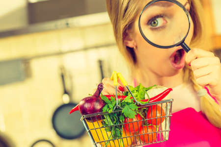 Woman using magnifying glass loupe, investigating shopping basket with many colorful vegetables. Healthy eating lifestyle, nutrients vegetarian food, searching for pesticides and chemicals. Stock Photo