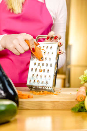 Unrecognizable woman grating carrot on metal grater, kitchen utensil making food preparing healthy vegetable salad.