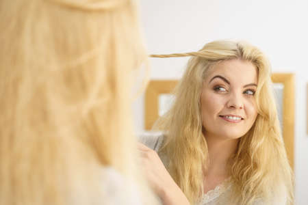 Happy positive blonde woman in bathroom during morning routine looking at herself in mirror styling hair. Stock Photo