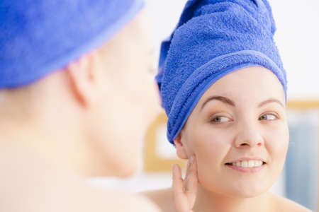 Pretty cheerful woman after taking a shower having wet hair covered in blue towel, looking at herself in mirror checking skin condition.