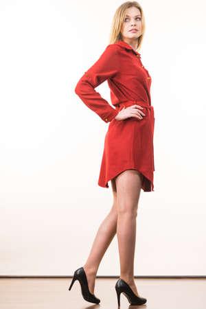 Super fashionale vrouw draagt elegante casual rode korte jurk en zwarte stijlvolle hoge hakken. Stockfoto