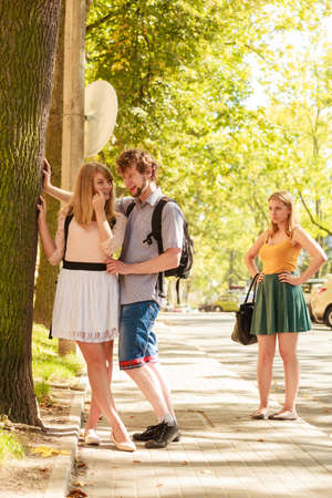 Jealous girl looking at flirting couple outdoor. Happy young woman and man couple dating. Summer romance affair. Stock Photo - 121268721