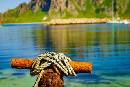 Harbor marina detail. Old rusty mooring bollard with rope. Bleik village, Andoya island, Vesteralen archipelago.