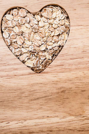 Dieting healthcare concept. Oat cereal oatmeal heart shaped on wooden surface. Healthy food for lowering cholesterol. Stok Fotoğraf