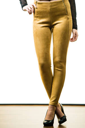 Unrecognizable woman wearing tight leggings pants mustard yellow brown well fitting skinny trousers Imagens
